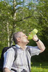 Hiker drinking water from bottle on forest trails