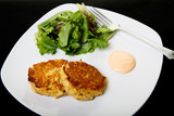 Two Crab Cakes in White Plate on Black