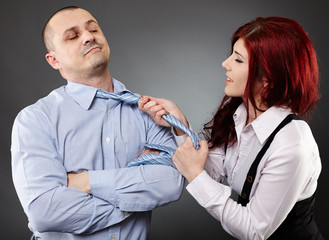Businesswoman pulling businessman's necktie