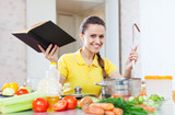 happy woman cooking  vegetables with book