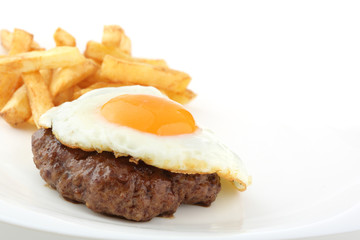 fried hamburger and egg isolated on a plate
