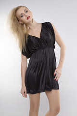 Young pretty woman with beautiful blond hairs in black dress