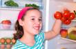 Mädchen holt Tomaten aus dem kühlschrank