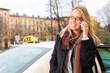 Junge Frau steht vor einem Taxi und telefoniert