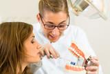 Zahnärztin mit Zahnbürste, Gebiss und Patientin