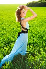 A young woman in a long blue dress enjoying nature