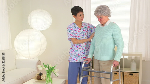 Chinese nurse helping elderly patient walk