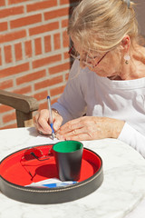 Senior woman writing his score on paper outdoor in garden. Playi