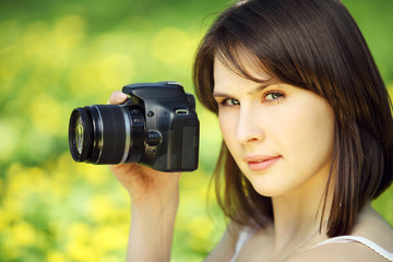Image of young beautiful woman photographing in summer park