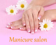 Woman hands with french manicure and flowers on pink towel