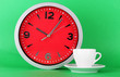 Cup coffee and clock on green background
