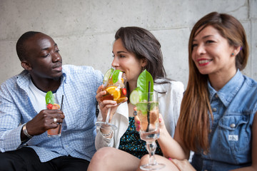 Three young people with cocktail at bar