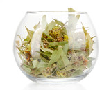 Dried herb in glass container isolated on white