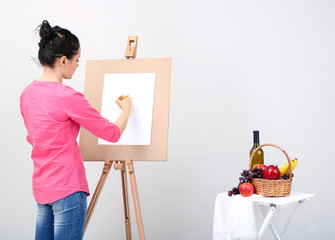 Beautiful young woman painter at work, on color background