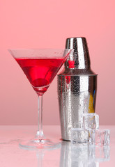 Cocktail shaker and cocktail on red background