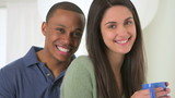 African American and Caucasian couple looking at camera