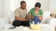 Happy African American and Caucasian couple using tablet pc on c