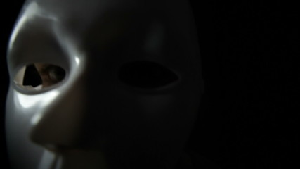 Spooky masked man over black background