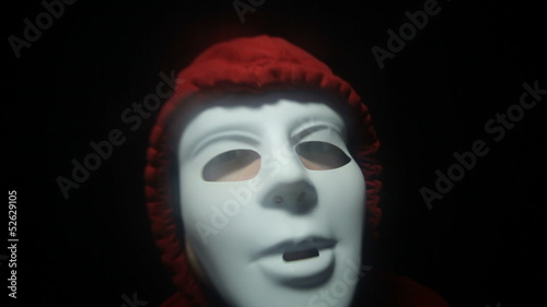 Furious masked man over dark background