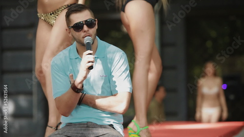 man speaks into a microphone in the background dancing girls