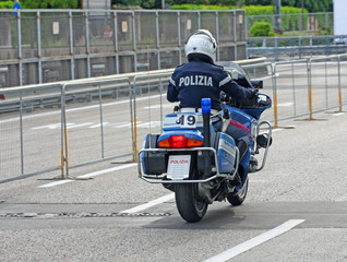 Italian State police motorcycle runs fast on the road to an emer