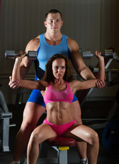Instructor assisting girl with dumbells