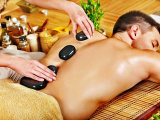 Man getting stone therapy massage .