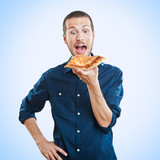portrait of a young beautiful man eating a slice of pizza marghe