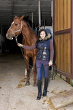 equestrian with her horse in stable