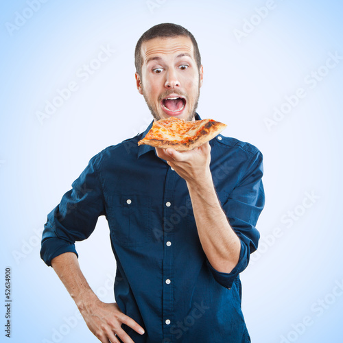 portrait of a young beautiful man eating a slice of pizza marghe - 52634900