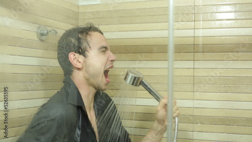 Funny businessman in shirt singing in shower