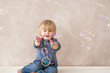 Funny little boy trying to catch colorful soap bubbles