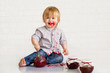 Adorable little boy got messy eating strawberry jam