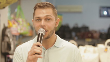 adult handsome man speaks into a microphone