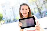 Cheerful girl in town showing tablet screen
