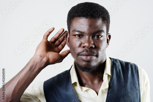 African American holds his hand near his ear and listening