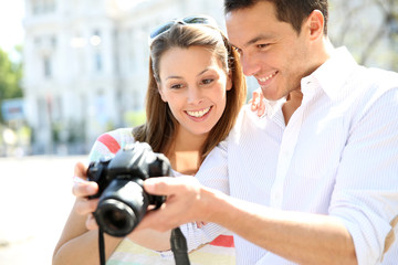 Happy couple looking at pictures on photo camera