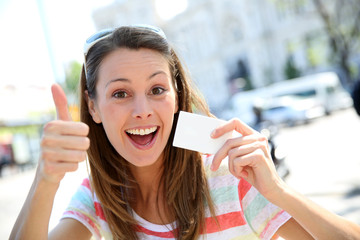 Cheerful girl in showing tourist pass