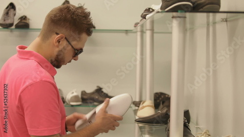 A handsome man chooses shoes at a store