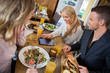 Woman Using Digital Tablet While Having Meal With Colleagues