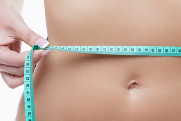 Female tummy with tape measure