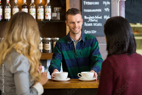 Bartender Serving Coffee To Female Friends At Cafe