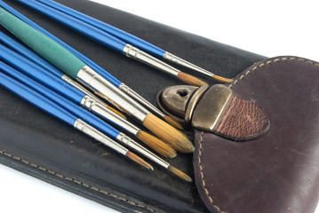 Leather case and paint brushes on white background