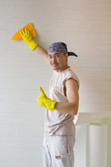 Young worker smoothing wallpaper with spatula