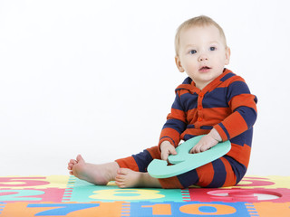 Charming baby boy sitting on carpet with numbers