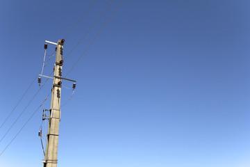Electricity concrete pylons against clear blue sky