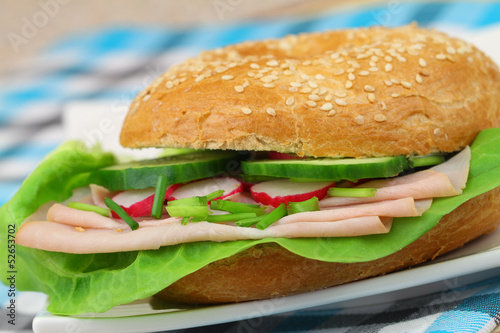Bagel with ham, lettuce, cucumber and radish, close up