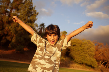 Boy celebrating at sunset