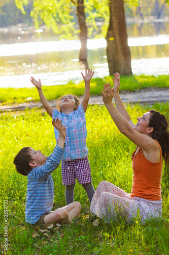 mom daughter and son sitting in outdoors at picnic meditate stre