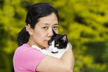 Mature woman holding large family cat outdoors